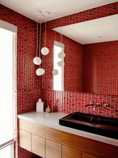 A powder room is covered in bright red tile.