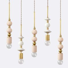 Our beaded pendants bridge jewelry and home decor in a playful and modern way. Two spherical tinted ceramic beads, in matte blush, navy or white - are strung together with contrasting brass hardware.