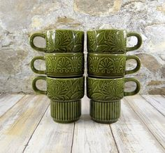 Retro set of six avocado/olive green stacking mugs. Great space saver for storing! The mugs are glazed and have embossed floral designs. Marked JAPAN on the bottom.  They measure 3.75H and 3 in diameter at the rim, Base is 2.25 in diameter.  They are in good vintage condition. Two have missed glaze marks on the rim. See photos.
