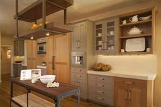 main wall of French industrial style kitchen with wood tone and gray cabinets