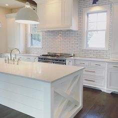 I have always been a sucker for a white kitchen and this one is no exception. That X detail on the...