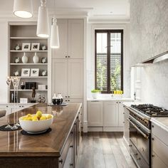 interesting idea for island, wood instead of stone.  love the marble walls & vent hood, also love the height