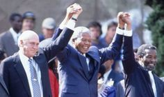 Nelson Mandela at his presidential inauguration with his deputies, Frederik de Klerk and Thabo Mbeki. Mandela (centre), the South African elected president and Frederik De Klerk, the last white South African president share a light moment at the swearing in of Mandela on 10 May 1994.