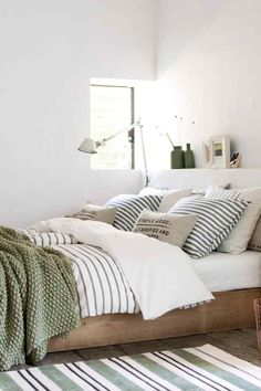 bright white bedroom with black and white striped bedding and green accents