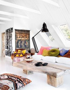 Very nice #eclectic mix. Rustic wood, black frame asymmetrical gallery wall. Colorful pops of pillows. Oversized couch. White walls.