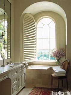 A Romantic Master Bath - Princess Yellow limestone  surrounds a bathtub. So pretty. Love the window.