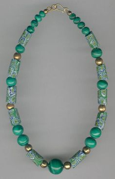 African-made Trade Bead Necklaces 1 - from ATB A beautiful subtly coloured 15 ins / 38 cm choker necklace containing nicely matched antique Venetian glass Millefiore cylinders - average size 17 x 9 mm Malachite stone 7 to 16 mm spheres - strung on Silver wire The 8 mm sphere spacers and the hook and eye fastening are Gold-plated tbn 257 £90