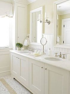 White Bathroom. I like the wood panel in the back.  I also like the framed mirrors.