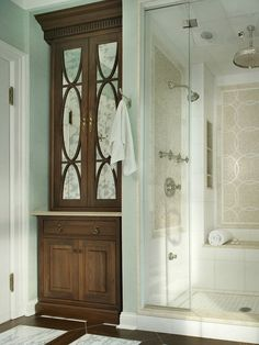 Built In Linen Closet in bathroom- gorgeous cabinet and wood color. Also love that shower, from the tile color and design combos to the nice large shower head!