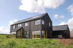 Single color house with color popping windows. black zinc sheeting modern house environmental design