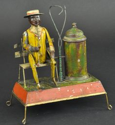 """GUNTHERMANN MAN SMOKING & SEATED ON BENCH Germany, a very curious painted tin example, clockwork activated, intense action involves smoke pushed through tube in shared smoke chamber which appears to come from gentleman's mouth as he lowers and raises his pipe, bellows appear below chamber which pushes the smoke, making this a truly amazing and rare toy. 10"""" h. Missing palm leaves, paint wear, repair to mechanism."""
