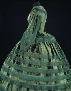Day dress  Place of origin: Great Britain, United Kingdom (made)  Date: 1855-1857 (made)  Artist/Maker: unknown (production)  Materials and Techniques: Silk plush trimmed with silk fringe and braid, bodice lined with silk and whalebone strips