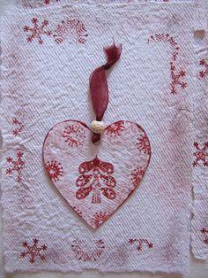 Postal navideña realizada con papel artesanal hecho por nosotras. Estampado de motivos navideños en rojo. El corazón se puede quitar de la postal para adornar cualquier rincón.