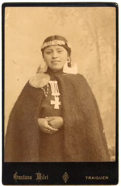 Photograph (black and white); Cabinet Card; a studio portrait of a young woman posed in front of a painted background of an outdoor scene; she wears a medella (coin-chain headdress),  quipan ( a square cloth, wrapped around the body), ikulla (shawl) or manta (blanket), chaway (earrings), tupu (clothes pin), trapelakucha (pectoral pendant), and a ring; Traiguen, Chile.  Albumen print