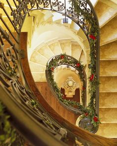 A limestone-and-iron spiral staircase looks striking when dressed in holiday garlands.