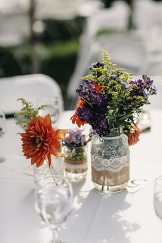 burlap and lace covered mason jars with florals captured by Heather Elizabeth Photography http://www.weddingchicks.com/2014/02/24/sweet-purple-and-orange-summer-wedding-at-a-california-vineyard/