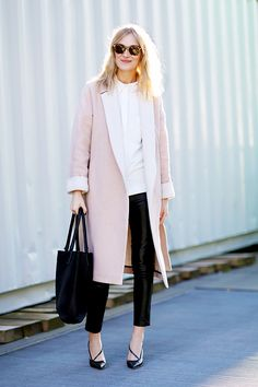 A pink coat is paired with a white button-down shirt, black pants, black heels, a black bag, and sunglasses