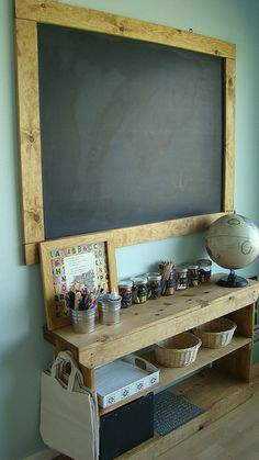 "Love the framed chalk board, shelving and canvas bags.  An area for kids crafts so they can ""work"" when mommy does....ALSO doubles as teaching space!!!"
