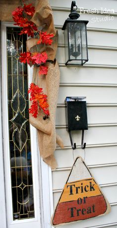 a Burlap Candy Corn makes a sweet addition to a Fall front porch  - Find more seasonal decorating tips at Fresh Idea Studio.com