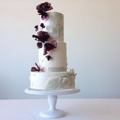 Not even my fancy camera was able to capture the way the light shined through these aubergine #ricepaperflowers and left bright purple reflections against the cake's stone colored finish. #coastalwedding #weddingcake #handmadeflowers #edibleflowers #tornpapereffect #jasminerae #art #edibleart #cake