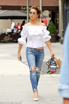 Bardot babe: Kate Beckinsale dressed to impress in a chic white bardot blouse as sheheade...