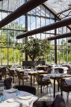 Tunnelmallinen De Kas -ravintola on kunnostettu kookkaisiin kasvihuoneisiin.