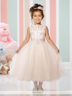 Style 216300 from Joan Calabrese for Mon Cheri is a sleeveless satin, lace and tulle tea-length full A-line flower girl's dress with jewel neckline, metallic lace overlay bodice, gathered tulle circle skirt with wire edged hem.