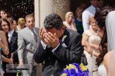 Greek Orthodox wedding, rice thrown at bride and groom, groom shielding eyes from projectile rice at Greek wedding.