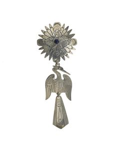 Brooch, used to attach a prayer shawl, in the form of a rayed disc from which hangs a peyote bird, in white metal (German silver alloy) with crystal, as used in the Native American Church: Americas, USA, Arizona, Pinon, Navajo, by Zaro Begay, 2008.