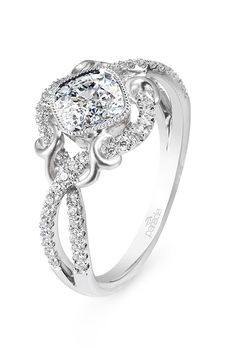 Brides.com: . Style R2771, diamond halo engagement ring with intertwined diamonds and 18K gold flourishes and a bezel set cushion center, $2,175, Parade Design