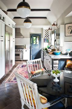 kitchen with dark floors, light walls, colorful rug, black, white, brass lighting, dark beams