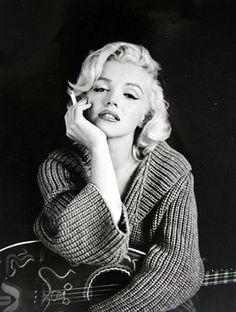 Marilyn monroe con una guitarra en sus piernas y fumando un cigarrillo