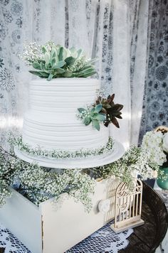 A wedding cake surrounded by baby's breath and succulents is a delicious cake to us! {@mytwinlens}