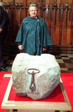 Kay Metheson standing behind Scotland's Stone of Destiny. Ms. Metheson was one of four Scottish nationalists who stole the stone from Westminster Abbey on Christmas Day, 1950. The stone, the coronation seat of Scottish kings, was taken from Scotland in 1296 by Edward I and made into the seat of the coronation chair for future kings of England. Ms. Metheson and 3 others stole the stone. In 1996 England officially returned the stone to Scotland.