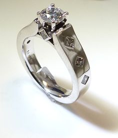 A modern engagement ring with princess cut diamonds up the sides.  www.troyshoppejewellers.com