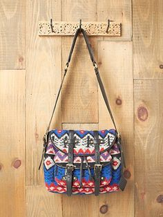 Peruvian Ski Satchel, by Mark & James.  Colorful printed bag with leather details and adjustable snap button closure. One front pocket and one zip back pocket. Printed fabric interior lining. One zipper pocket and one open patch inside.  $327.35