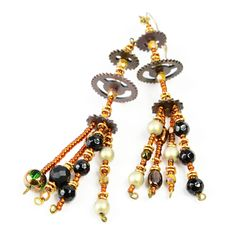 "Celebrate the turn of the 19th century in style. It's never too late to look great! These ""gear""rings are a must-have for fashion-forward steampunk ladies. Copper-toned chandelier earrings are four inches long. They are sisters, not twins. Each includes three bronze gears arranged on a foundation of glass seed beads. A complementary array of statement beads (along with two beads exclusive to each earring) includes Czech fire-polished glass, antiqued gold glass and faceted glass ..."