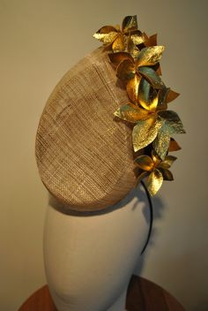 Gold thread sinamay headpiece with gold leather flowers.