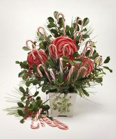 Candy canes and lollipops nestled among evergreens cut from your yard create a whimsical holiday centerpiece that's quick and easy to assemb...