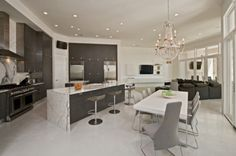 The kitchen, dining and family areas are all designed to function together as a large, open expanse; the continuous ceiling and use of glass help achieve this goal. The dark kitchen cabinets anchor the space visually, while an antique chandelier serves as the only embellished counterpoint to the sleek, contemporary design of the space.