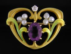 A striking Krementz Art Nouveau brooch with pastel enamel leaves and pearl clusters surrounding a regal amethyst.  A small diamond sparkles at the top of the brooch.  Created by Krementz & Company in 14kt gold, circa 1900