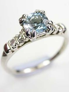 Vintage Aquamarine Ring with Split Prong Design, RG-3445, The diamonds of this vintage ring slink down the shoulders, allowing the split prong set aquamarine the center stage. A sleek polished band provides an understated backdrop.  Details: Vintage. Circa 1940 or later. 14k white gold. Round single cut diamonds; 0.06 carats. Round cut aquamarine; 0.58 carats. Ring Size 5.75