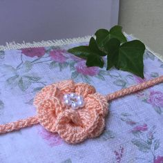 Little crochet flower with crystal and plastic pearl in the middle. Very cute and nice, best accessory for you little cutie. On back with elastic skinny lace. Yarn microfiber acrylic, very soft and comfortable to wear, specially for delicate baby skin.  Made to order after purchase. Allow 3-5 business day before shipping. Available another 30 colors... Color may be slightly different due to monitor settings.  Please note size on notes to seller at checkout.