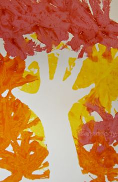 Fall Hand Print Art - Exploring Negative Space with Kids from www.fun-a-day.com.  A twist on the tried-and-true fall hand print tree.