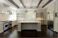 classic kitchen design and materials ... beamed ceiling; marble counter and backsplash; awesome center island; light filled.