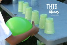 Minute-to-Win-It Game = Use a balloon to move cups past a masking tape line