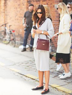 Light grey shirt, light grey shorts, burgundy bag, loafers, sunglasses, and silver watch