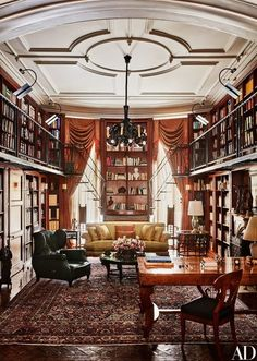 The double-height library is an ode to Solomon's love of books. The windows and Couturier-designed sofa are dressed in silk damask | archdigest.com
