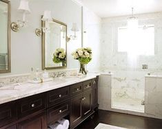 Calcutta gold marble, espresso finishes, Love the mosaic tile the lines the the shower and then tops the sink counter.