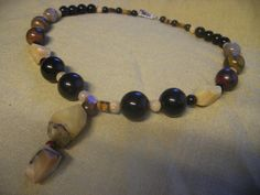 This is a special necklace made for my son Dominic, using stones Mom collected thru the years, Onyx, Tiger Eye, Marble and Tiger Iron beads were used. Enjoy!  Pegs